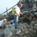 Figure 7. Excavation foreman M. Kasotakis washing a wall before application of the mortar (Photo: Azoria Project)